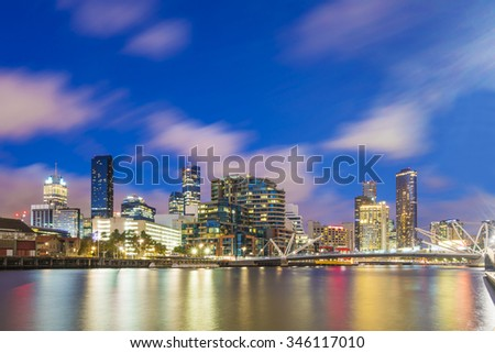 Cityscape of Dockland in Melbourne at sunset, long expsure, blurring clouds and smooth water - stock photo