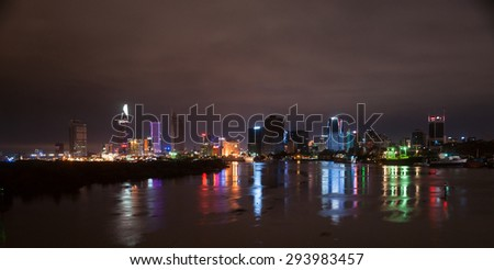 Cityscape of Ho Chi Minh at night with bright illumination of modern architecture, viewed over Saigon river in Southern Vietnam.