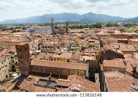 Cityscape of Lucca, Italy. Seen from the Torre delle ore with the Lucca cathedral in the background - stock photo