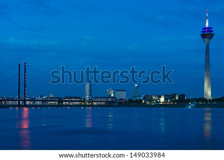 Cityscape of night Dusseldorf over the Rhine river - stock photo