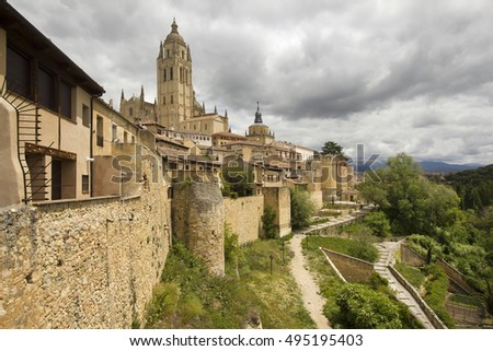 Cityscape of Segovia with the cathedral on the hill, the ancient city walls and other buildings and trees in Spain