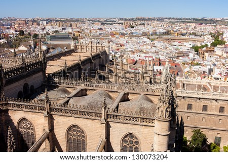 Cityscape of Seville in Spain, on the first plan Gothic style rooftop of Seville Cathedral, El Arenal historic quarter and Triana district at the far end.