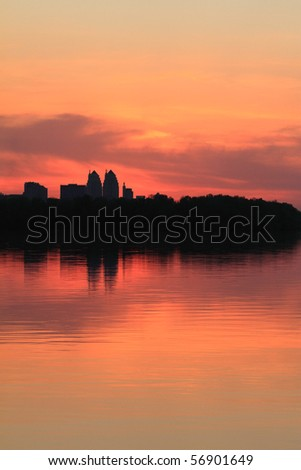cityscape of sunset scenery with building silhouette and river reflection