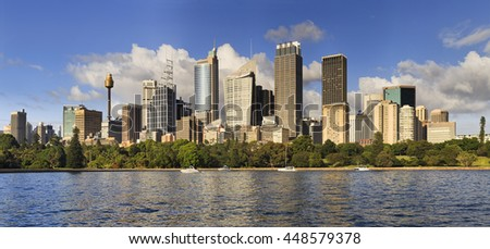 Cityscape of Sydney. Modern architecture of CBD rising above green belt of plants in Royal Botanic Garden across Harbour Farm Cove.