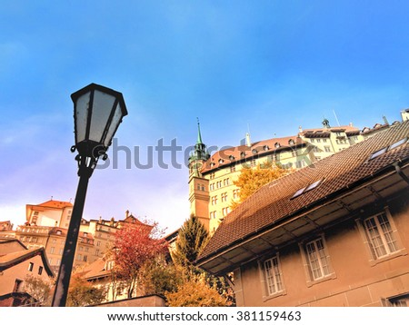 Cityscape of the old town in Fribourg, Switzerland, including a traditional street light, numerous houses and the city hall in background