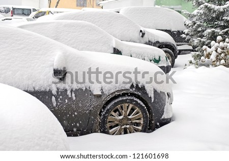Cityscape - parked cars covered with snow - stock photo