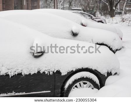 Cityscape - parked cars covered with snow in winter - stock photo