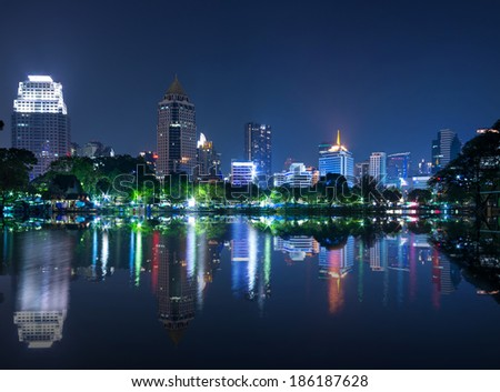 cityscape reflect with lake view in the park at twilight time.