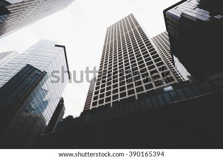 Cityscape view with business buildings with contemporary architecture in metropolitan city in day. High-rise modern skyscrapers in big town against grey sky - stock photo
