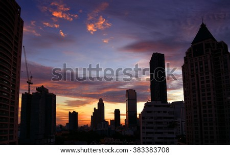 cityscape with evening sunset sky, silhouette of buildings