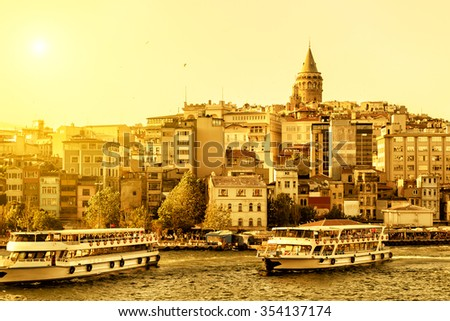 Cityscape with Galata Tower over the Golden Horn with tourist boats in Istanbul, Turkey - stock photo