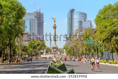 CIUDAD DE MEXICO, DF / MEXICO- FEBRUARY 3 2014: A changing landscape. Sunday´s bikers in Paseo de la Reforma at El Angel. In the background, the new Bancomer Tower building under construction. - stock photo
