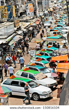 CIUDAD DEL ESTE, PARAGUAY - DECEMBER 13: Typical crowd of taxis in downtown on December 13, 2011 in Ciudad Del Este. The city is known for its free trade area and the usual mess and crowd. - stock photo