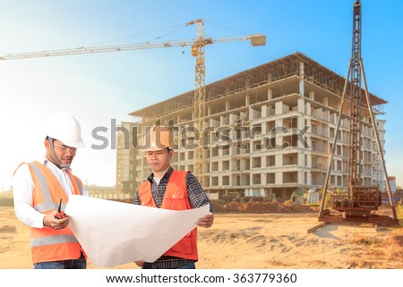 Civil Engineer and Foreman control working at construction building site