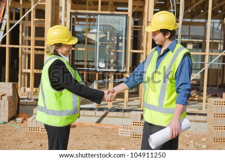 civil engineer and worker shaking hands at the construction site - stock photo