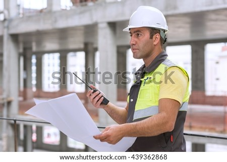 Civil Engineer at construction site is inspecting ongoing production according to design drawings. - stock photo