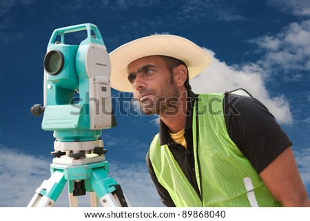civil engineer doing land survey at a construction site, close up of surveyor working on theodolite