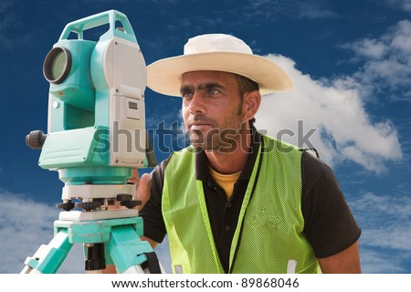 civil engineer doing land survey at a construction site, close up of surveyor working on theodolite - stock photo