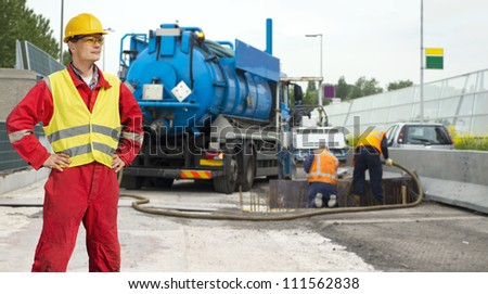 Civil engineer posing in front of road works, where a concrete foundation is poured into the foundation of the road - stock photo