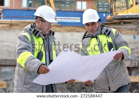 Civil Engineers at at construction site are inspecting ongoing production according to design drawings.