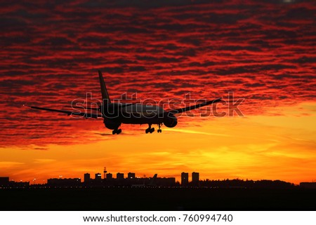 Civil wide-body airliner landing during sunset with amazing sky on background.