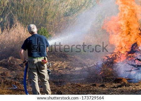 civilian man extinguishing fire with a hose - stock photo