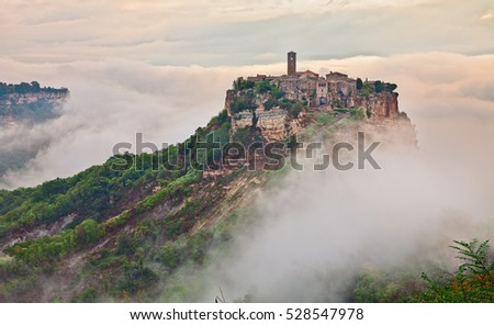 Civita di Bagnoregio, Viterbo, Lazio, Italy: picturesque landscape at dawn of the ancient village shrouded in fog on the steep tuff hill