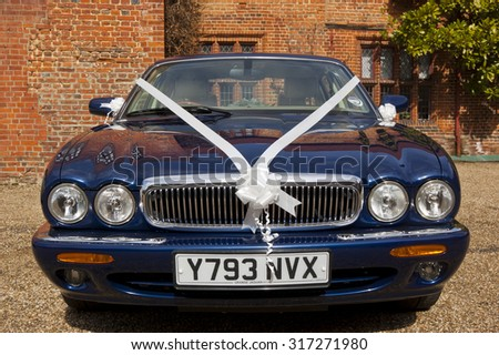 Clacton-on-sea, Essex, England, UK: 21 June 2014- A  jaguar wedding car with white ribbon decorations, about to go to the brides house.
