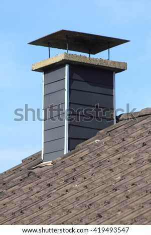clad in slate shingles chimney, blue sky in background
