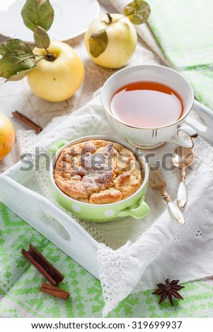 Clafoutis apple on a tray. Breakfast with pudding and tea on a white tray