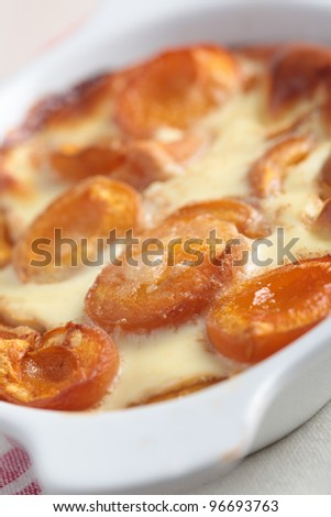 Clafoutis with apricot in a baking dish. Shallow DOF