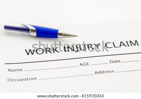 Claim form for an injury at work with pen on white background.