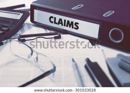 Claims - Ring Binder on Office Desktop with Office Supplies. Business Concept on Blurred Background. Toned Illustration. - stock photo