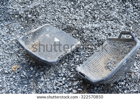 clam-shell shaped basket on pile crushed stone at construction site - stock photo