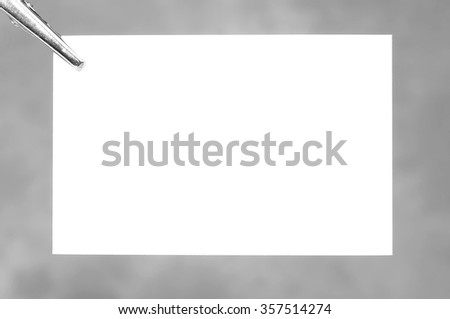 Clamp holding blank business card  - stock photo