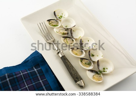 clams in white wine and parsley in rectangular plate on a rustic wooden table - stock photo