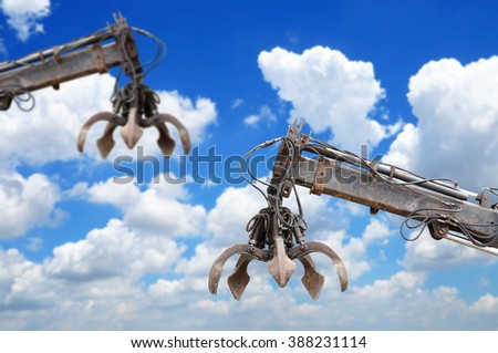 Clamshell and Hydraulic crane with blue sky - stock photo