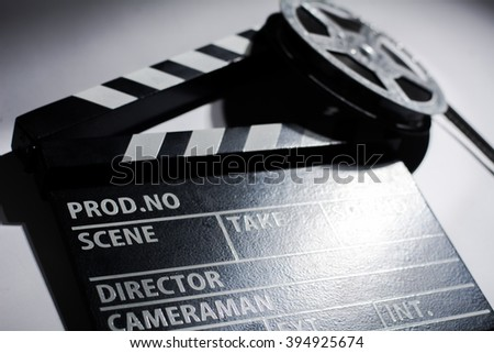 Clap cinema on the table. Metal reel of film - stock photo
