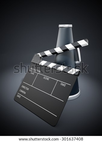 Clapboard and bullhorn on black spotlit background