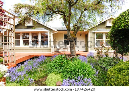 Clapboard siding house exterior. View of wooden deck and flower bed with blooming plants and trees