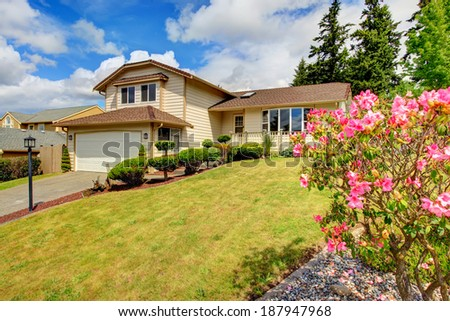 Clapboard siding house with tile roof. House with beautiful curb appeal and blooming trees