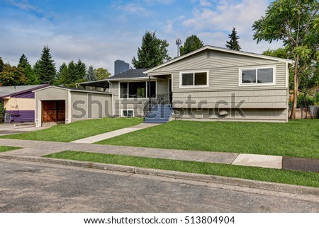 Clapboard siding one story house exterior on a sunny day. Grass filled front yard. Garage with opened door. Northwest, USA