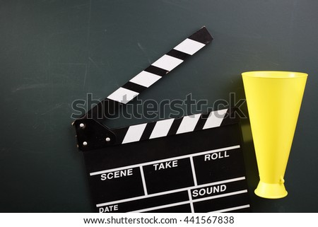 clapper board and megaphone on the blackboard - stock photo
