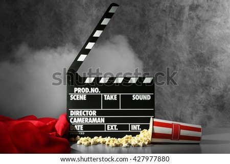 Clapper board and pop corn on wall background - stock photo