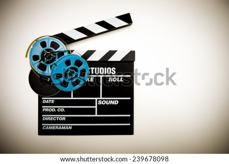 Clapper board with 8mm film reels in white background and vintage color effect - stock photo
