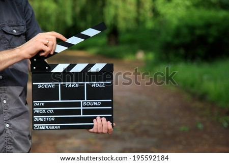 clapperboard in hand - stock photo