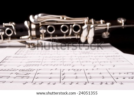 Clarinet isolated over sheet music - focus on the sheet music - stock photo