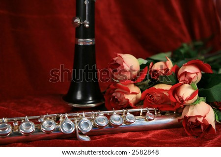 Clarinet,silver flute and bouquet of roses on red velvet background
