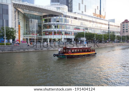 CLARKE QUAY, SINGAPORE - MARCH 26 : Tourist boat cruising the Singapore river on MARCH 26,2014 in Singapore. The Singapore River has been the centre of trade since Singapore was founded in 1819 - stock photo