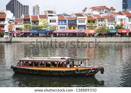CLARKE QUAY, SINGAPORE - MAY 11: Tourist boat cruising the Singapore river on May 11 2008 in Singapore. The Singapore River has been the centre of trade since Singapore was founded in 1819 - stock photo